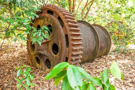 Large rusty gear of Tin Dredge in the deserted tin mine. Dry leaves fall on the ground, tropical forest backgrounds. Thai Mueang, Phang Nga, South Thailand. Banque d'images