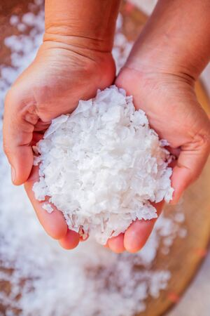 Pure white crystals salt, rock salt in women hands on crystals backgrounds. Top view, close-up. Traditional rock salt making of Bo Kluea, Nan, Thailand. Ancient salt pits. Food culture, history. Stok Fotoğraf