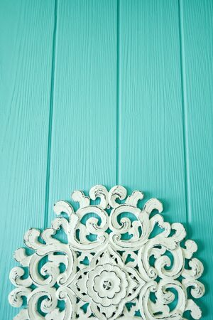 Beautiful white carved wooden backrest on wood mint color background. Classic caribbean style.