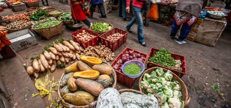 A variety of local vegetables and fruits in a daily market at, Yunnan, China. Winter fruits and vegetables. Food culture. Selective focus. Banco de Imagens