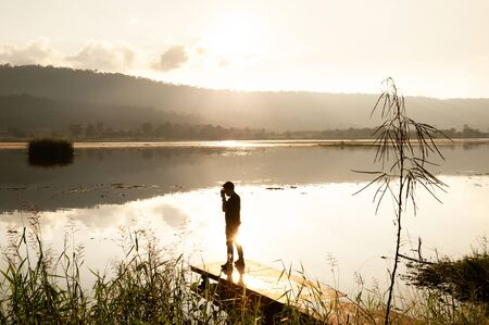 Winter by the lake, traveler man standing on the terrace and enjoying lake view with camera at sunset, scenic of lake and mountains backdrop, bright and glittering surface of water. Khao Yai, Thailand.
