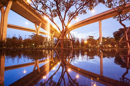 Highway interchange landscape, underneath view of the Bhumibol Bridge at sunset, beautiful shape of architecture reflecting on water, tropical park with pool and fountain foregrounds. Thailand.