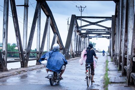 Khmer people riding motorcycles and bicycle across over the old French Bridge over the Praek Tuek Chhu River on rainy morning, daily life in Kampot, South Cambodia. Motion blur.