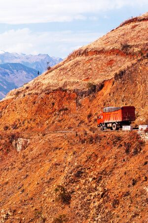 Red truck driving on a mountain road on winter dusk, fantastic landscape of red mountain ridge and snow mountains on backdrop, remote location in South China. 스톡 콘텐츠
