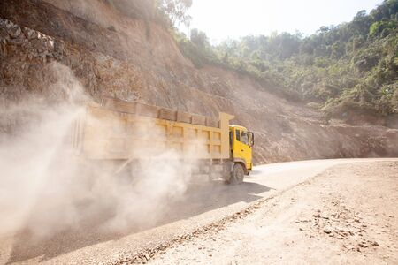 The yellow dump truck working on the dusty mountain road at construction site, a new road construction in North Laos near Laos-Vietnam border. Development project.