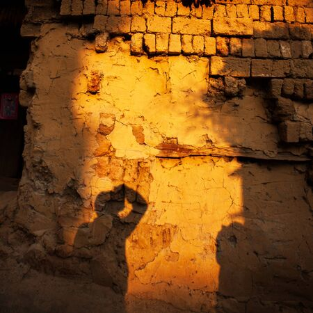Shadow of a photographer on earthen wall of ancient chinese house at dusk, dried corn cobs hanging over the ancient earthen wall, beautiful sunset light, Chengzi Village, the ancient village of Yunnan, China. Фото со стока