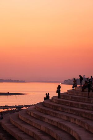 Tourists and Laotians relaxing on the pier by the Mekong River during serene sunset, fantastic colors of sky on winter evening, public park in Vientiane, Laos.