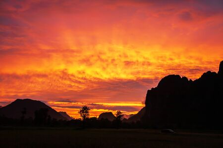 Dramatic clouds above a limestone mountain range, colorful ripple clouds on sunset sky, fantastic winter scene in Vang Vieng, North Laos.