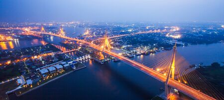 Soft focus, aerial view of Bhumibol Suspension Bridges and highways interchange over the Chao Phraya River at dusk, beautiful light trails across the bridges and river curve. Samut Prakan, Thailand. Фото со стока