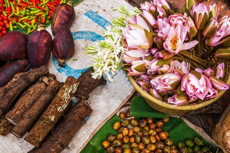 Top view, fresh tropical vegetables and fruits at the daily market in Luang Prabang, Laos, water lily flowers and wild flowers, red hot chili peppers, banana flowers, wild plants and hog plums on banana leaves.