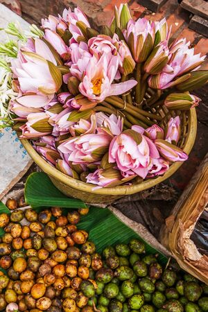 Top view, fresh tropical vegetables and fruits at the daily market in Luang Prabang, Laos, light pink water lily flowers and hog plums on banana leaves.