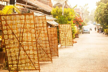 lots sheet of rice paper on bamboo racks for natural drying on the street of Luang Prabang, traditional Laos dishes, bright winter evening. Food cultures.