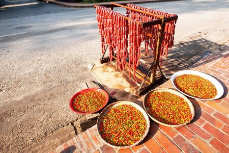 Sausages and Red Laos chili peppers on the bamboo baskets for natural drying on the sidewalk of Luang Prabang, Laos 스톡 콘텐츠