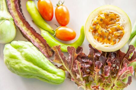 Organic fruits and vegetables, half passion fruit, red oak lettuce, tomatoes, sweet peppers, purple winged bean, chayote and eggplants on white paper background. Top view, closeup. Focus on passion fruit.