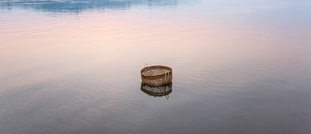 Peaceful serene by river, a bamboo basket is dipping in the Mekong River on winter morning, picturesque scene of sunrise sky reflecting on gently water, retro still life in rural North Laos. Фото со стока