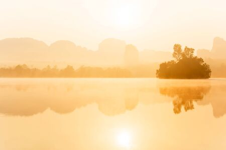 Scenery landscape of tropical lake in the morning mist, golden sun shining down on the lake and mountain range backdrop, beautiful gently mist and reflection on surface of freshwater, Nong Talay, Thailand.