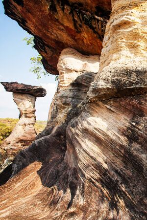Mushroom rock, fantastic shape and layers in sandstone of mushroom rock, scenery landscape of ancient sandstone in very ancient times, bright sunlight on summer dusk, Pha Taem, Thailand. Фото со стока