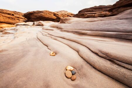 Zen meditation in nature, beautiful pebbles and lines in sandstone, balance and harmony, scenery landscape of the steep of Mekong River on summer dusk. Фото со стока