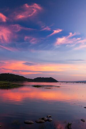 Defocus. Beautiful twilight sky above a tropical lake, gently light pink clouds against the blue sky at dusk, soft reflection of clouds on surface of freshwater, rural scene in West Thailand.