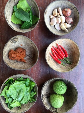 Authentic Thai red curry past recipe with ingredients in coconut shells on old wooden, red hot chili peppers, bergamot fruits and leaves, garlic and herb. Food culture. Top view. Flat lay pattern.