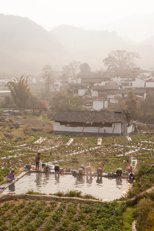 Peaceful village. Scenic ancient village landscape, a group of chinese woman washing at the old pool in potato's field in the mist. Mountains in the mist backgrounds. Yunnan, rural of South China. Soft morning light.