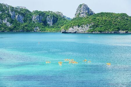 Aerial view, a group of tourists kayaking in the blue ocean at summer day, tropical islands backdrop. Mu Koh Ang Thong National Park, Surat Thani, Thailand.