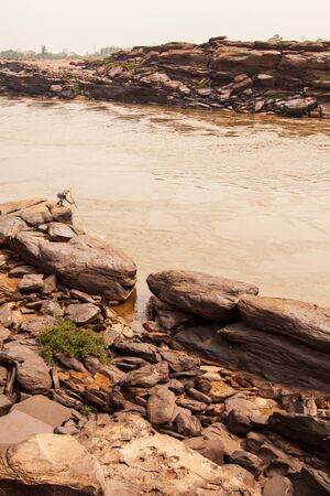 A local fisherman casting the fishing net in the Mekong River, fantastic scenery of steep sandstone cliff by the river on summer evening, rural life near Thailand-Laos border.