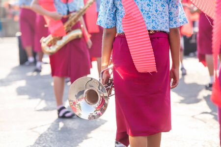 Thai high school band in traditional clothing preparing for marching Thai New Year's national holiday or Songkran festival. Focus on the trumpet.