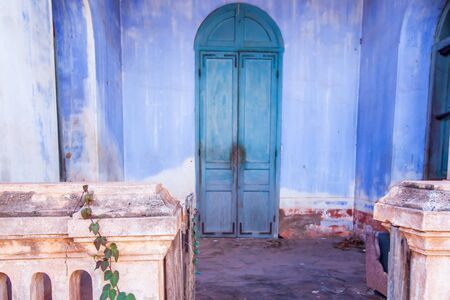 Ancient facade of abandoned colonial residential building, vine plant growing on old stoop, old cerulean blue wall and arctic blue wood door blurred backgrounds. Ban Tharae, Thailand. Focus on old stoop.