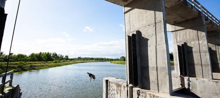 Happy asian boy jumping of concrete spillway into the canal on a hot summer day. Agriculture concepts.
