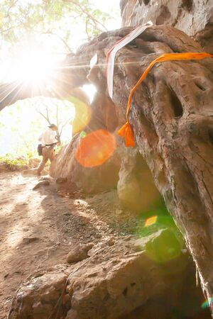 Fantastic wild tree's root with prayer flags on the cliff path to the Tham Pi Man or spirit cave, contain prehistoric wooden coffins, ancient mysterious cave of Mae Hong Son, Thailand.