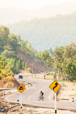 An asian man cyclist in hill climbing in the morning, a cyclist riding uphill on a mountain road. Sport, Recreation concept. Focus on road sign.
