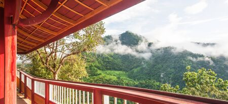 Tranquil mountains view from long iron balcony, picturesque of tropical mountain range in misty rainy, warm sunrise shines on the branches of wild trees. Banco de Imagens
