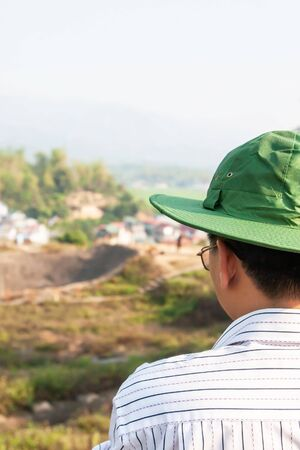 Rear view of male Asian tourist standing while looking at the crater of A 1 hill in Dien Bien Phu, the most important camp of the French colonists during the first Indochina War in 1954. Vietnam. Selective focus.