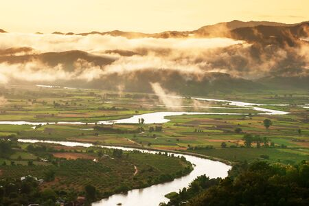 Picturesque valley with Kok River in the morning mist, golden sunrise shines through ripples mist on a mountain range in the background, a tranquil landscape near Thailand and Myanmar border. Stock Photo