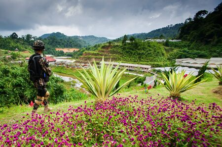 Rear view of asian special forces soldier in camouflage uniform, protected helmet with gun in hands during security patrol pass flower garden, mountains and cloudy in the backgrounds. 版權商用圖片
