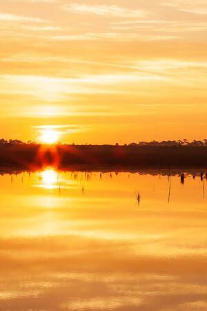 Glowing sun setting into pine forest and wonderful autumn lake, bright star ray from the sun and ripple clouds reflection on the lake. Vacation, Meditation concepts.