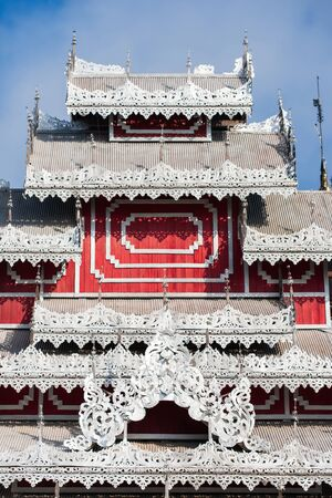 Elegant carved silver tin tiles, roof and window awnings of ancient buddhist temple. Wat Phrathat Doi Kong Mu, Mae Hong Son, Thailand. The temple is open to the public. Foto de archivo