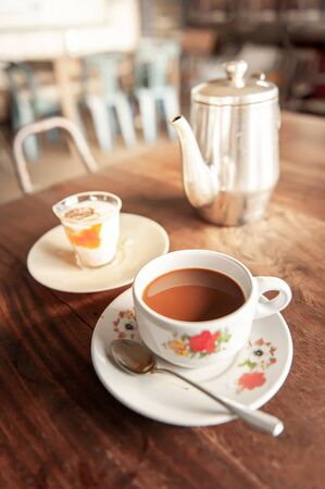 Relaxing in an old coffee shop in early morning, vintage a cup of coffee with soft boiled egg and tea kettle are on old wooden table. Focus on a cup of coffee.