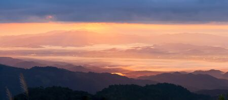 Panoramic view of idyllic mountain range at sunrise, glowing sunbeam shines through blue clouds on the valley and river in early morning mist, scenery of Northern Thailand.