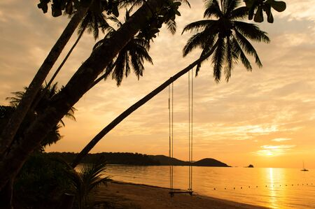 Scenery of a tranquil tropical island on summer dusk, silhouette of coconut palm trees and swing against dramatic sunset sky. Koh Mak Island, Thailand.