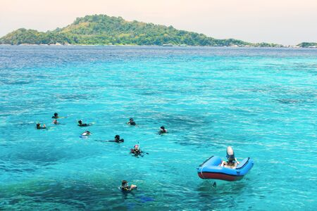 A group of divers in diving suit staying afloat in the sea for a dive at Similan Islands, tourist attractions in South Thailand.