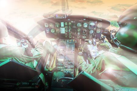 Military helicopter cockpit with two pilots flying against sunset over a lake and mountain range. Focus on control panel. 免版税图像
