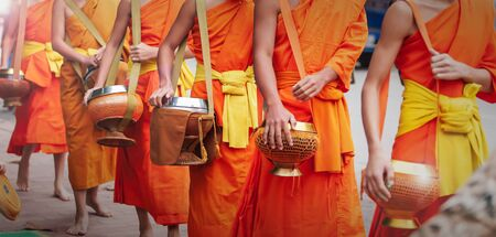 Close of Buddhist novice monks carrying their alms bowls for going on almsround in early morning. Luang Prabang, Laos.