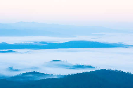 Serene scenery of mountain range on winter morning, soft mist covered blue mountains and valley, landscape near Thailand and Myanmar border. Soft focus on the mountains.