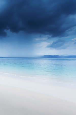 Dramatic dark storm cloud over the sea, view looking from a tranquil beach on an island. Environment, Climate change concepts. Soft focus on the storm cloud.