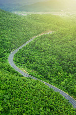 Aerial view of mountain road at sunrise, curves asphalt road through mountain range and green forest.