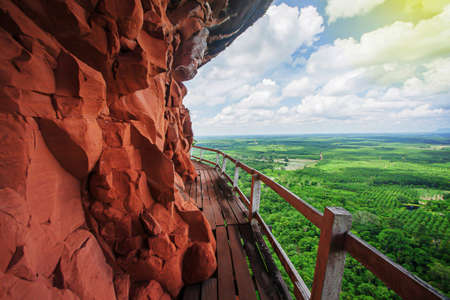 Empty old wooden bridge on the edge of red sandstone cliff, green fields and white clouds in the backgrounds.