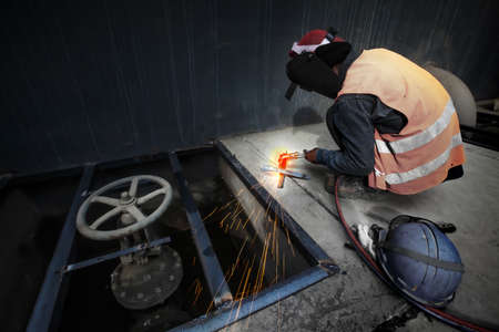 Asian man welding a metal grate, arc welding process with sparks. Long exposure. Focus on sparkling.