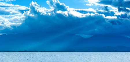 Dramatic rain clouds covers the lake and blue mountains, lightbeam shines through rain clouds onto the lake. Phayao Lake, North Thailand. Focus on clouds. Фото со стока